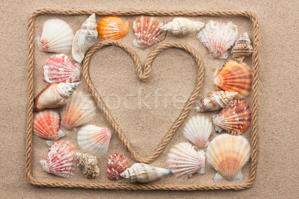 Symbolic heart made from rope and sea shells lying on the sand Stock photo © alekleks