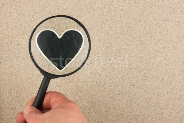 Hand with magnifying glass over the heart in the sand Stock photo © alekleks