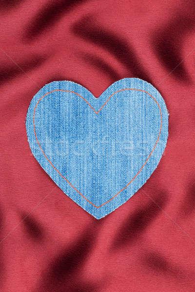 Heart made of denim fabric with yellow stitching on red silk Stock photo © alekleks