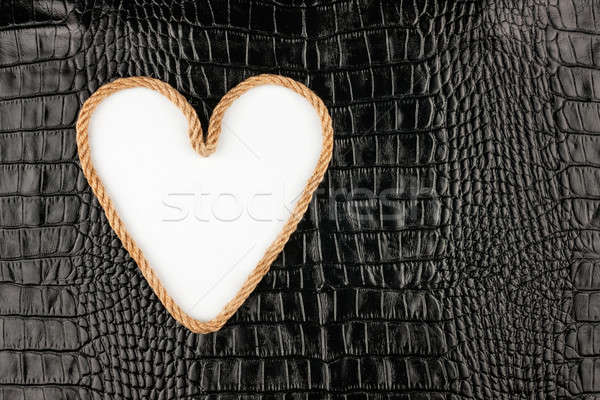 Symbolic heart made of rope lying on a crocodile leather  Stock photo © alekleks