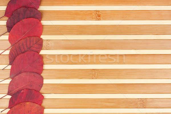 Red autumn leaves lying on a bamboo mat Stock photo © alekleks