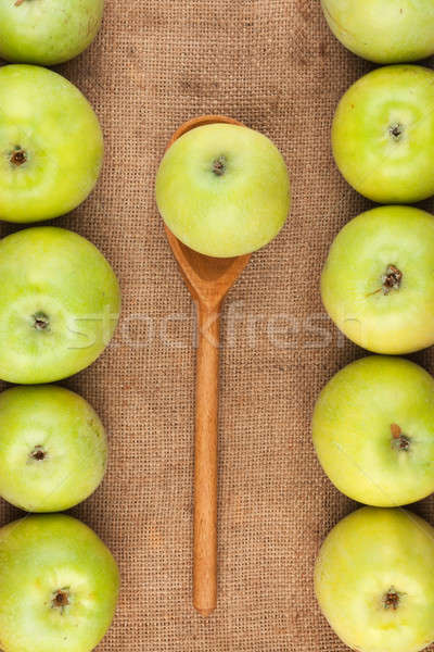 Spoon with green apple lying on the sackcloth among green apples Stock photo © alekleks