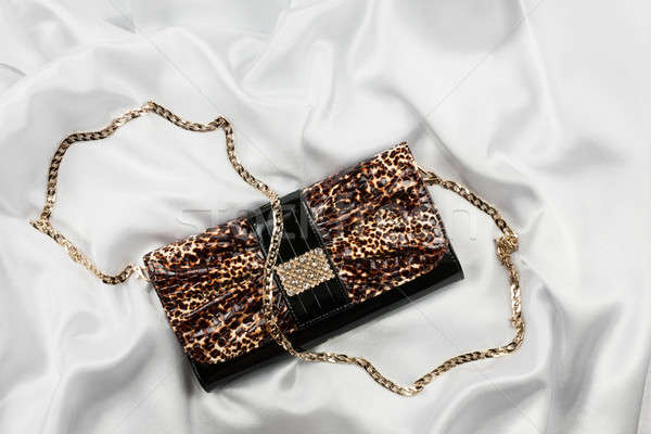 Leopard lacquer bag lying on a white silk Stock photo © alekleks
