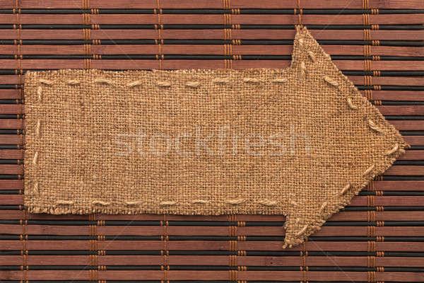Arrow made of burlap lies on a bamboo mat Stock photo © alekleks