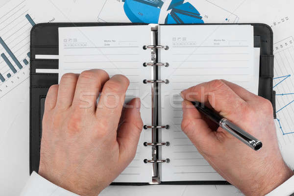 Male hand with pen wrote in a diary Stock photo © alekleks