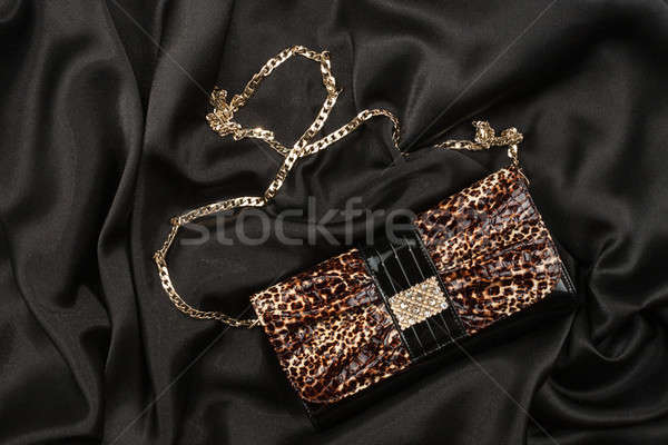 Leopard lacquer bag lying on a black silk Stock photo © alekleks