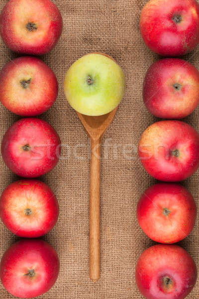 Spoon with green apple lying on the sackcloth among red apples Stock photo © alekleks
