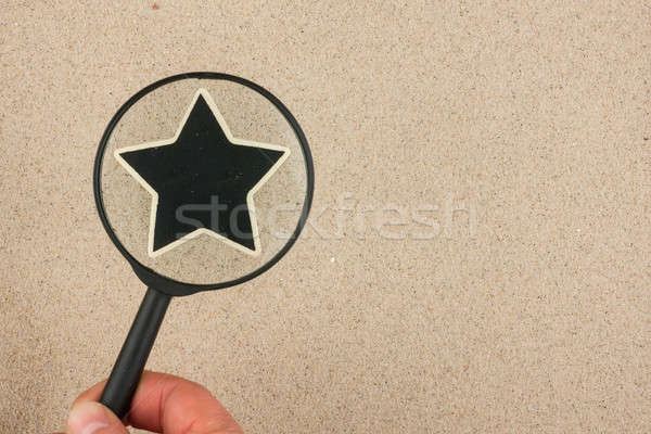 Hand with magnifying glass over the star, in the sand Stock photo © alekleks