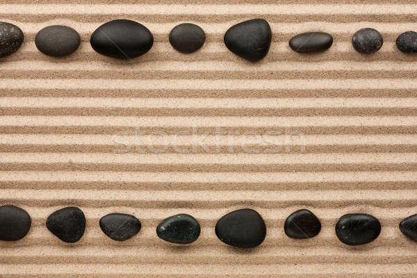 Two rows of black stones  on the sand Stock photo © alekleks