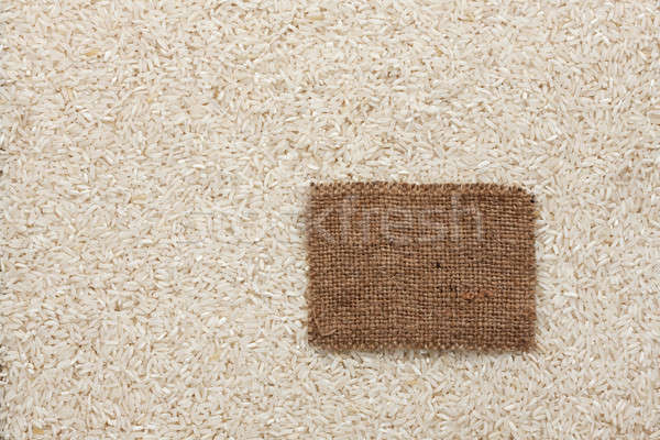 Tag made of burlap lies against the backdrop of rice Stock photo © alekleks