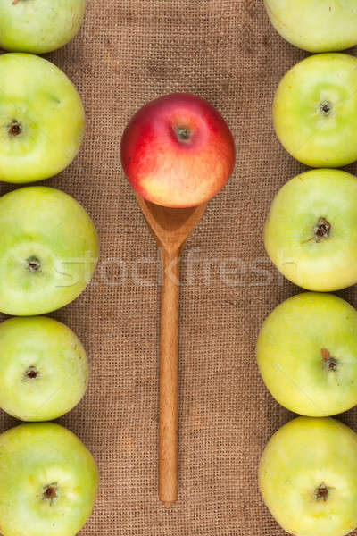 Spoon with red apple lying on the sackcloth among green apples Stock photo © alekleks