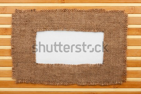 Frame made of burlap with white background lying on a wooden sur Stock photo © alekleks