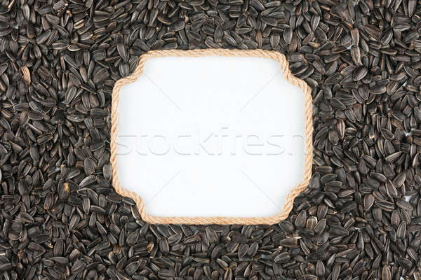 Figured frame made of rope with  sunflower seeds  lying on a whi Stock photo © alekleks
