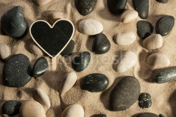 Close-up of stones and heart sticking out of the sand in the sun Stock photo © alekleks