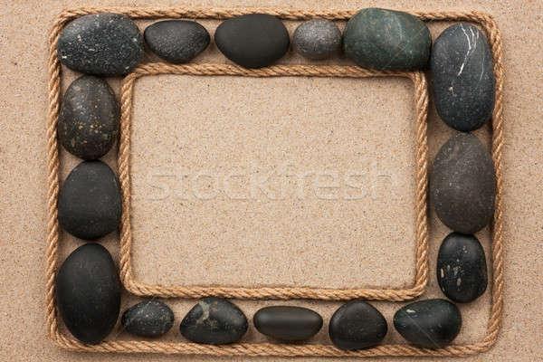 Gyönyörű keret kötél fekete kövek homok Stock fotó © alekleks