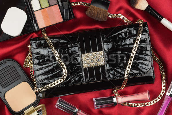 Beautiful bag from patent leather and cosmetics lying on red sat Stock photo © alekleks