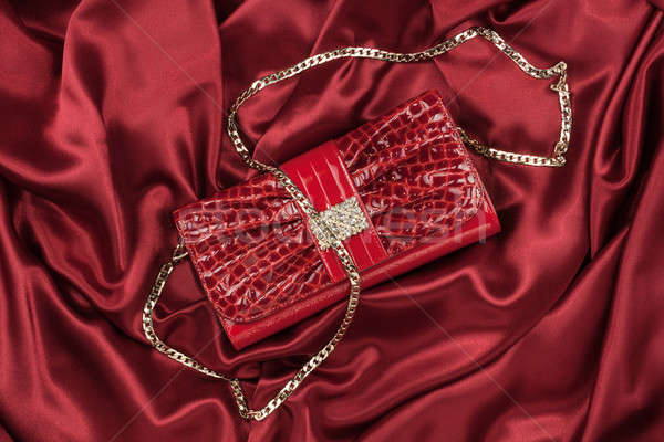 Red lacquer bag lying on a red silk Stock photo © alekleks