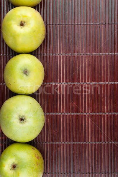 Green apples lie on dark bamboo mat Stock photo © alekleks