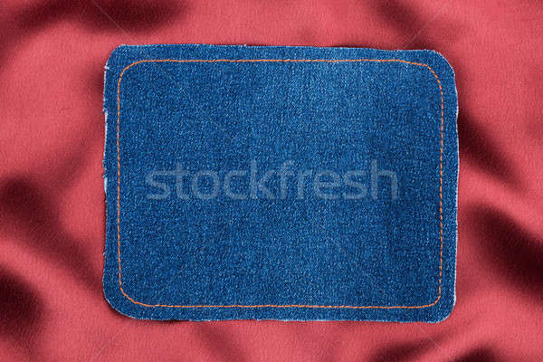 Frame made of denim fabric with yellow stitching on red silk Stock photo © alekleks