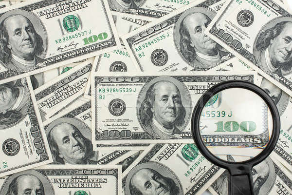 Stock photo: Look through a magnifying glass on the money