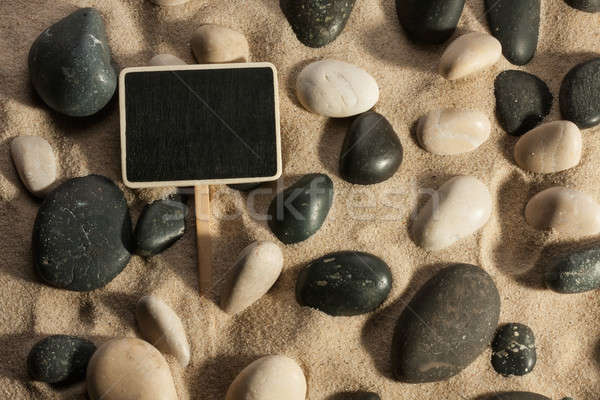 Close-up of stones and sign sticking out of the sand in the sunl Stock photo © alekleks