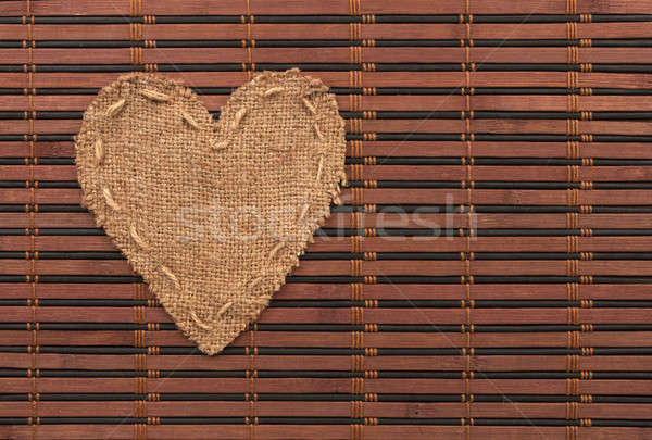 The symbolic heart of burlap lies on a bamboo mat Stock photo © alekleks