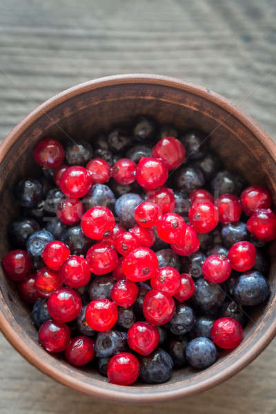 Bowl of blueberries with redcurrant on the wooden table Stock photo © Alex9500