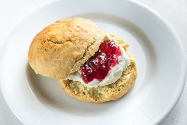 Scone with cream and cherry jam on the plate Stock photo © Alex9500