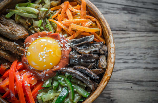 Bowl of bibimbap on the wooden table Stock photo © Alex9500