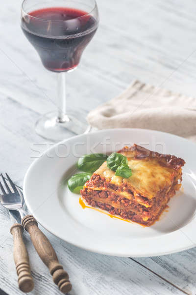 Portion of lasagne with a glass of wine on the wooden table Stock photo © Alex9500
