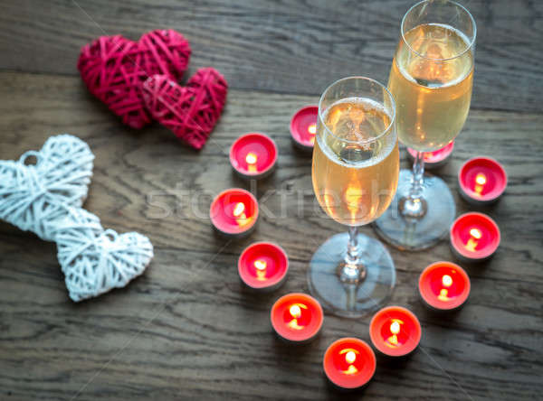 Two glasses of champagne inside of burning candles Stock photo © Alex9500