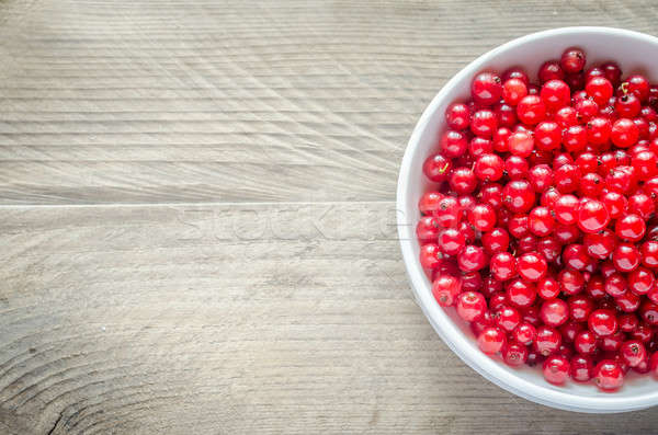 Bowl with fresh redcurrant on the wooden table Stock photo © Alex9500