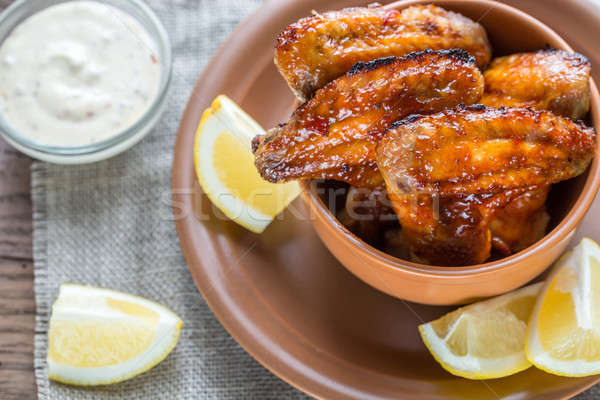 Caramelized chicken wings with glass of beer Stock photo © Alex9500
