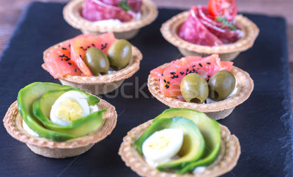 Stock photo: Tartlets with different fillings on the stone board