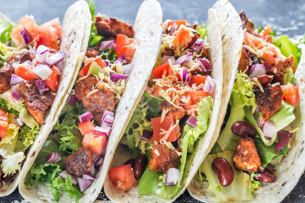 Four mexican tacos on a black background Stock photo © Alex9500