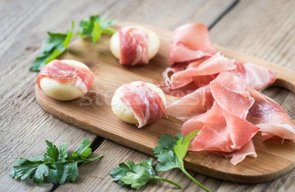 Mini cheese and prosciutto wraps on the wooden board Stock photo © Alex9500