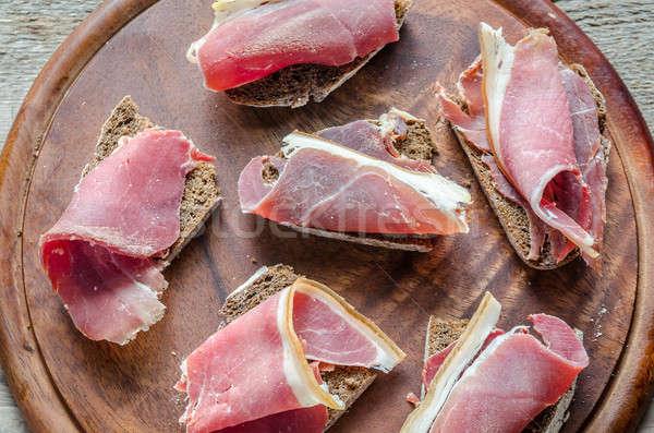 Slices of italian ham on the wooden board Stock photo © Alex9500