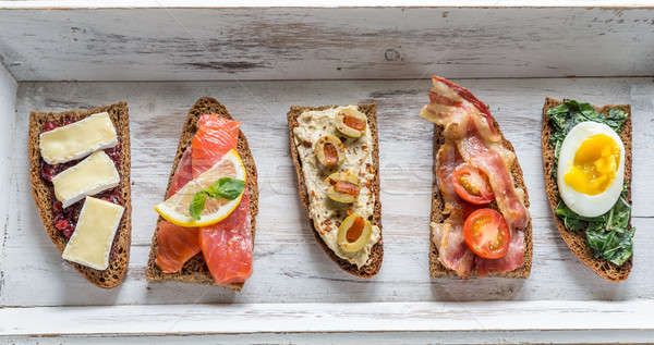 Bruschetta with different toppings on the wooden tray Stock photo © Alex9500