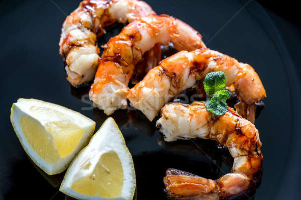 Fried shrimps with lemon wedges on the black background Stock photo © Alex9500