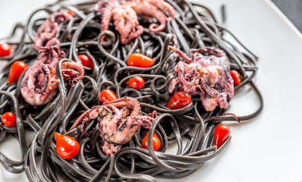 Pasta with black cuttlefish ink and small octopuses Stock photo © Alex9500