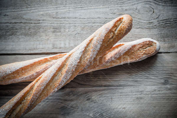 Two wholewheat baguettes on the wooden background Stock photo © Alex9500