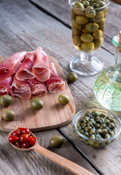 Jamon with capers and olives on the wooden board Stock photo © Alex9500