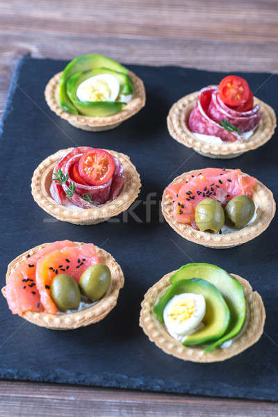 Tartlets with different fillings on the stone board Stock photo © Alex9500