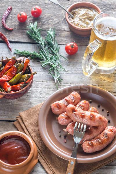Grelhado salsichas aperitivos caneca cerveja festa Foto stock © Alex9500