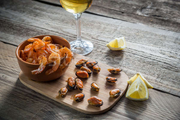 Stock photo: Fried shrimps and mussels with glass of white wine