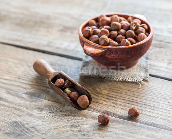 Bowl of hazelnuts on the wooden board Stock photo © Alex9500