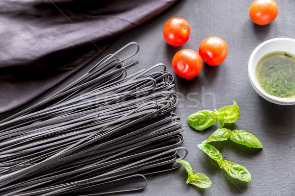 Raw black pasta with basil and tomatoes Stock photo © Alex9500
