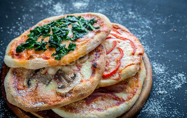 Mini pizzas with various toppings on the wooden board Stock photo © Alex9500
