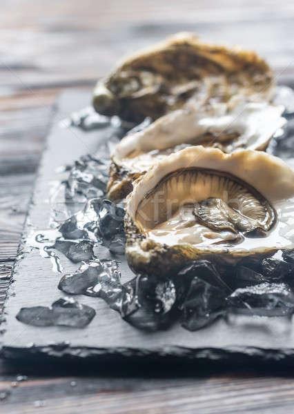 Nyers osztriga fekete kő tábla étel Stock fotó © Alex9500