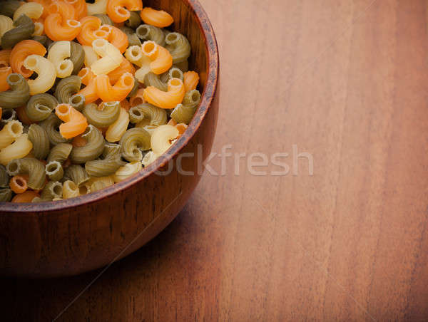 Stock photo: Uncooked pasta in a wooden bowl. warm color toned